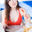 Beautiful latin girl eating fast food while working on laptop — Stock Photo