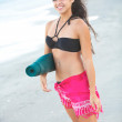 Beautiful happy female holding yoga mat at the beach — ストック写真