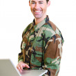White male in army uniform on lap top smiling — Stock Photo