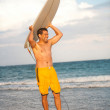 Hispanic male with surfboard at the beach — Stock Photo