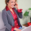 Beautiful business woman holding laptop talking on cellphone — Stock Photo