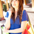 Beautiful latin girl with shopping bags thinking — Stock Photo