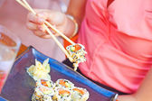 Woman Holding Sushi With Chopsticks — Stock Photo