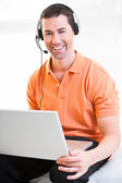 Happy business male on laptop with headset on smiling — Stock Photo