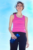 Smiling female in sports clothing holding water bottle. — Stock Photo