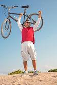 Hispanic male holding up mountain bike in victory — Stock Photo