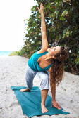 Pretty woman doing yoga at beach — Stockfoto