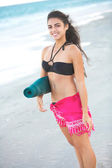 Beautiful happy female holding yoga mat at the beach — Stock Photo