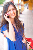 Beautiful young latin girl on cell phone with shopping bags — Stock Photo