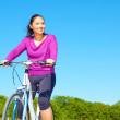 Playful young woman in casual wear sitting on bicycle — Stock Photo