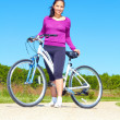 Playful young woman in casual wear sitting on bicycle — Stock Photo #30186193