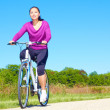Playful young woman in casual wear sitting on bicycle — Stock Photo #30186235