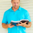Man with Tatoo Reading The Bible — Stock Photo
