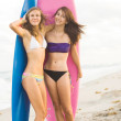 Stock Photo: Happy teenage girls at the beach with surfboards smiling