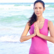 Beautiful female doing yoga warrior pose at the beach — Stock Photo #30429465