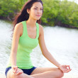 Beautiful female doing yoga warrior pose at the beach — Stock Photo