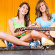 Happy cute teenage girls listening to music — Stock Photo