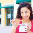 Stock Photo: Young Woman Eating Frozen Yogurt
