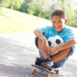 Little boy With Soccer Ball Sitting On Skateboard — Stock Photo
