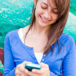 Stock Photo: Cute happy teenage girl text messaging