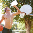 Young man on basketball court hydrating himself — Stock Photo