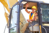 Portrait of young construction worker driving forklift waving — Stock Photo