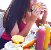 Happy Young Pretty Woman Eating a Delicious Cheeseburger — Stock Photo