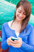 Cute happy teenage girl text messaging — Stock Photo