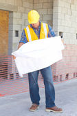 Serious Construction Worker Examining Blueprint At Site — Stock Photo