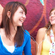 Stock Photo: Female Friends Listening Music
