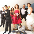 Stock Photo: newlyweds with bridesmaids and groomsmen jumping on bed