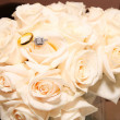 Foto Stock: Wedding Rings On White Roses