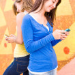 Cute teenage girls texting one another — Stock Photo