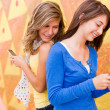 Cute teenage girls texting one another — Stock Photo #30430305