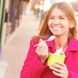 Stock Photo: Happy Young Pretty Female Eating Frozen Yogurt
