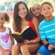Stock Photo: Siblings With Holy Bible At Park
