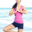 Stock Photo: Beautiful female doing yoga warrior pose at the beach