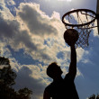 Silhouette of young man playing basketball — Stock Photo