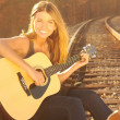happy beautiful young woman with guitar on railroad tracks — Stock Photo