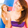 Happy teenage girls at the beach with surfboards smiling — Stock Photo