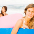 Happy teenage girls at the beach with surfboards smiling — Stock Photo #30430493