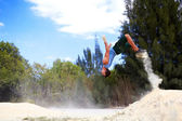 Young man doing back flip in sand — Stock Photo