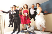Newlyweds With Bridesmaids And Groomsmen Jumping On Bed — Stock Photo