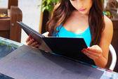 Jonge vrouw lezen menukaart — Stockfoto