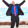 Happy businessman at the beach — Stock Photo