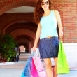 Beautiful smiling young woman walking with shopping bags wearing sunglasses. — Stock Photo