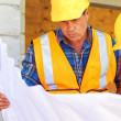 Architect and foreman reviewing blueprint together at construction site. — Stock Photo