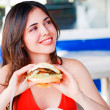 Beautiful happy young latin girl eating hamburger — Stok fotoğraf