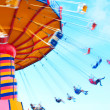 People swing past with motion blur, shot to convey some of the excitement of the midway ride. — Stock Photo