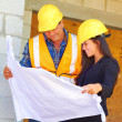 Architect and foreman reviewing blueprint together at construction site. — Stock Photo #32941533
